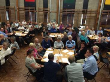 Patients in a large hall seated in groups around tables.
