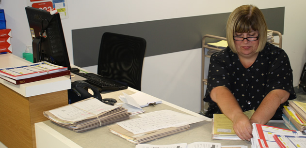 reception staff member at a desk with some patient notes
