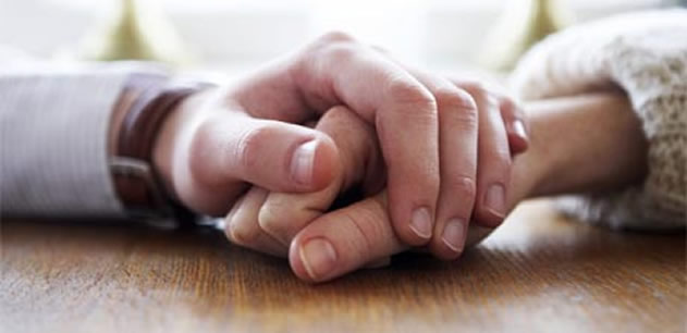 Picture of a pair of hands holding each other and resting on a table.
