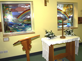 Picture of the hospital's chapel room, showing the two stained-glass windows, lecturn and floral display