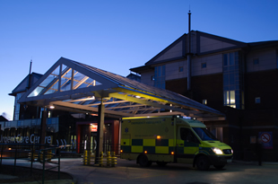 Emergency Department Entrance at night with an ambulance parked outside
