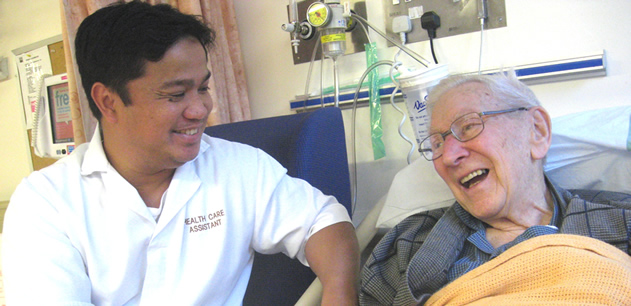 Smiling health care assistant talking to a patient who is in bed and laughing.