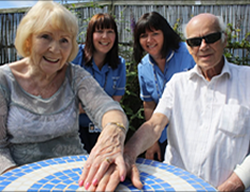two elderly patients holding hands with two nurses in the background