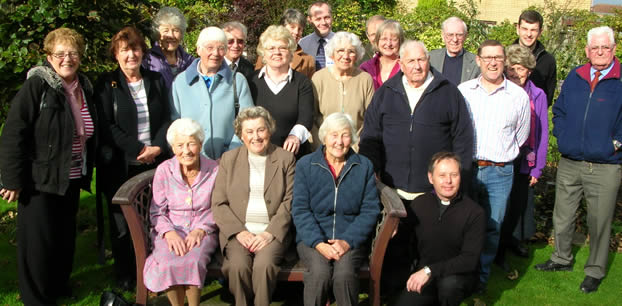 Chaplaincy volunteers - large group of volunteers pictured in the hospital grounds, some are seated on a bench.