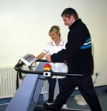 Patient using a treadmill with the assistance of a Physio