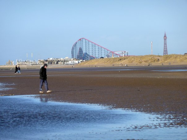 A man walking along Blackpool beach on his own
