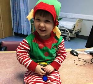 A small boy dressed as an elf on a hospital ward