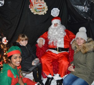 A young mum and her daughter with Santa and an elf in a grotto