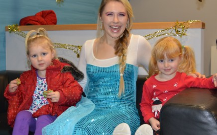 Woman dressed as Elsa from the film Frozen with two little girls