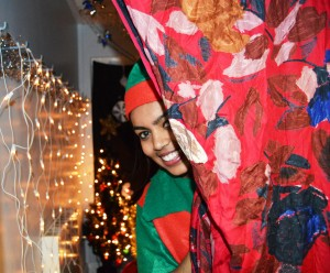 A woman dressed as an elf in Santa's grotto