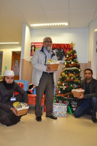 Three men with Christmas hampers next to a Christmas tree on a hospital ward