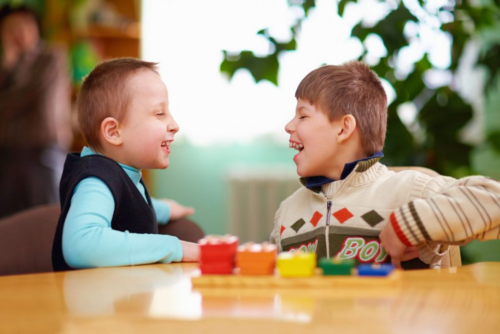 Two young children playing with plastic bricks and laughing