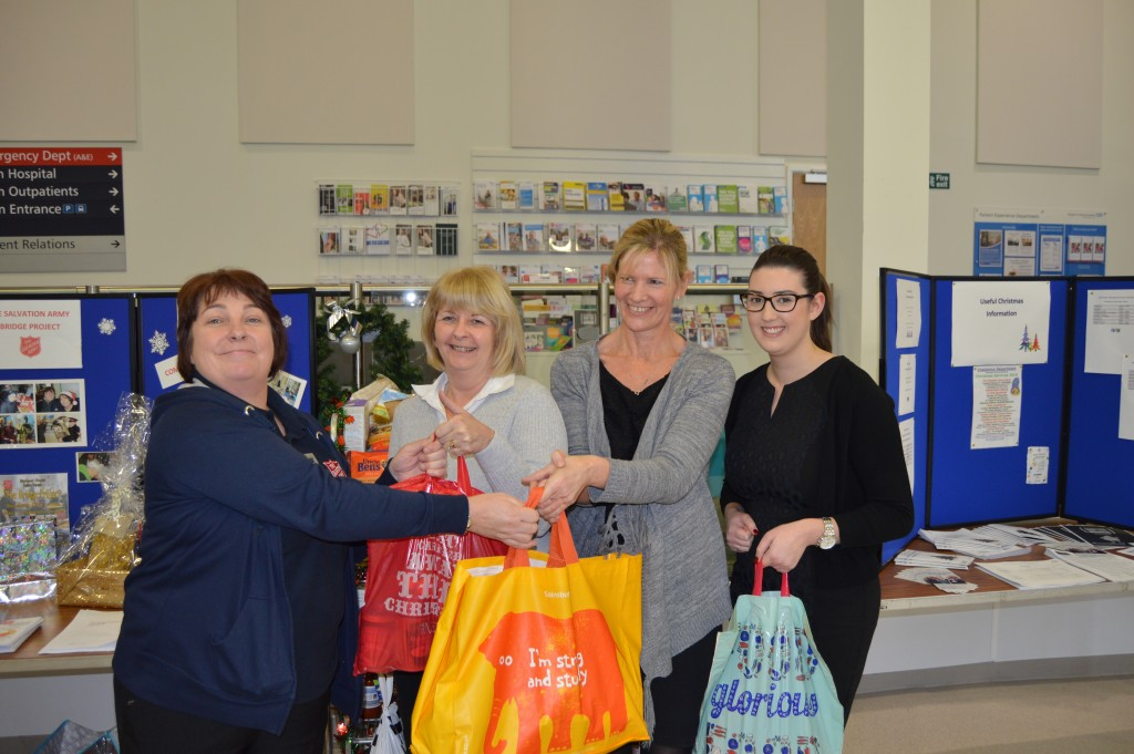 A women from the Salvation Army receive donations in a bag from three women who work at the hospital