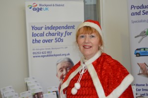 A woman dresses in Santa-style red festive clothing on a stall at the donation event