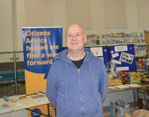 A man standing next to a sign for Citizens Advice