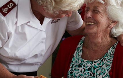 A Salvation Army workers gives a plate of food to an elderly woman