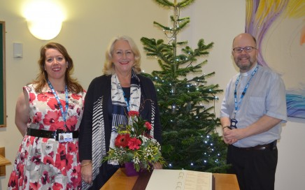 A chaplain and two women standing next to a Christmas tree