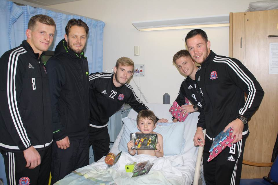 five footballers with a patient in his bed and some presents