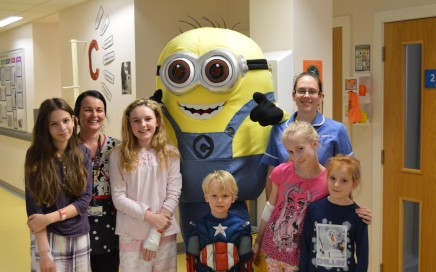 a group of young children with two nurses and the Minion character