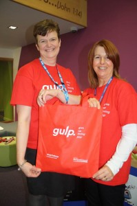 Two women holding a red bag with the word Gulp written on it