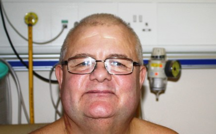 A man sitting next to medical machinery