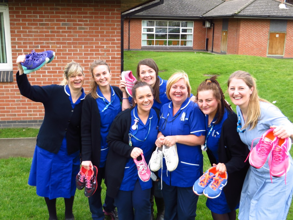 A group of nurses standing outside a buiding waving running shoes in the air