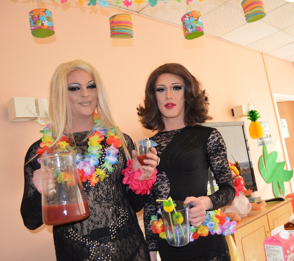 Two drag queens holding cocktails