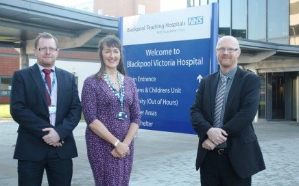 Three people standing next to a hospital sign