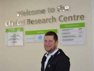 A man standing in front of a sign saying Clinical Research Centre