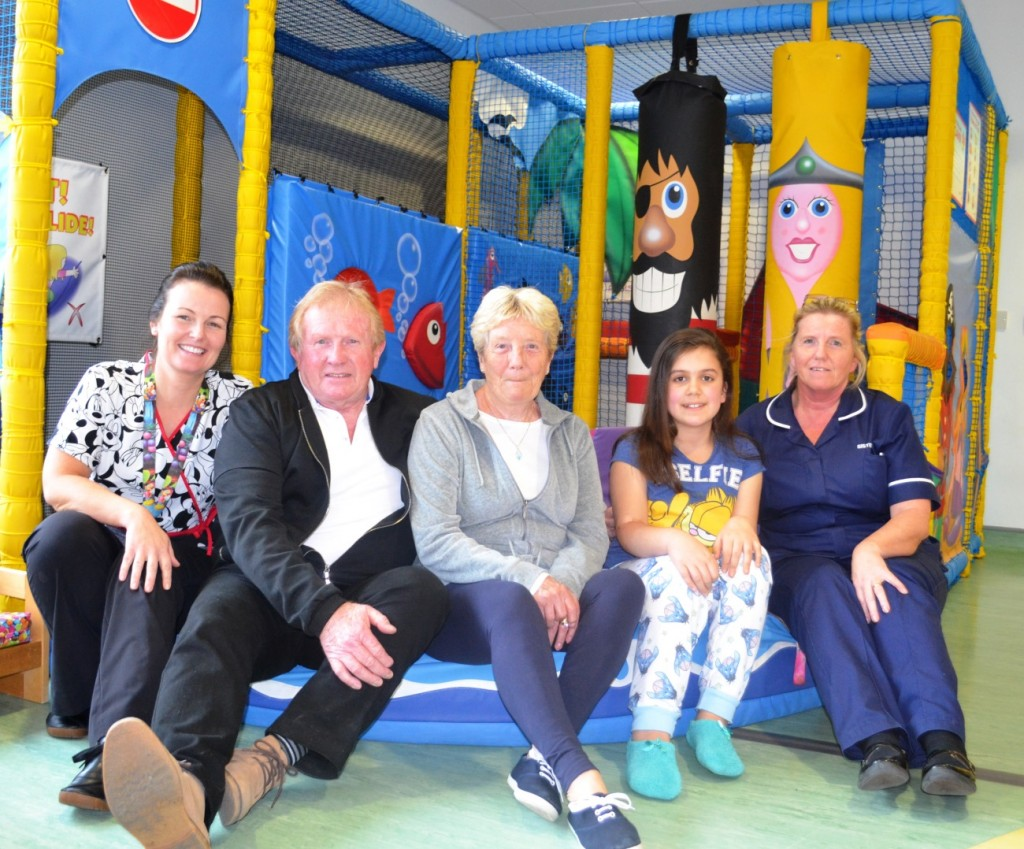 Richard and Linda Rayton visit their daughter Janette Smith, Play Worker Rosanne Norman and patient Pheobe Andrews on the Children's Ward to donate money raised in celebration of their Golden Wedding