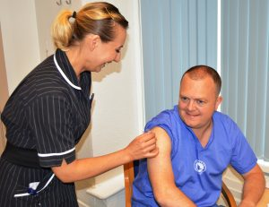 Occupational Health Nurse, Luba Elson, gives Cardiac Theatres Nurse, Neil Berrigan, his flu jab